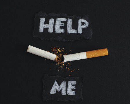 help me: Unhealthy habit. Broken cigarette on a black background with words: Help me. Conceptual image. Close-up.