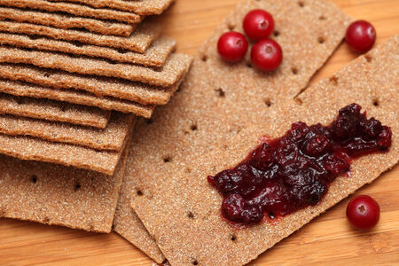crispbread: Healthy breakfast. Crispbread with cranberry sauce. Close-up. Stock Photo