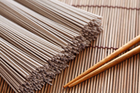buckwheat noodle: Raw soba noodles and chopsticks on bamboo napkin. Soba is a type of thin Japanese noodle made from buckwheat flour. Close-up.