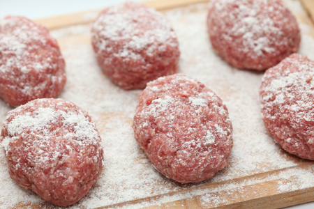 Raw pork and beef patties. Shallow depth of field. Close-up.