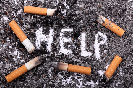 bad habit: Unhealthy habit. Cigarette butts on ash background with word: Help. Conceptual image. Close-up.