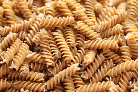 Raw brown pasta (Fusilli) background. Close-up.