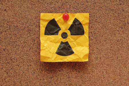 straight pin: Crumpled adhesive note with Radioactive Sign on corkboard (bulletin board). Stock Photo