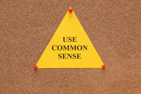 Triangular paper note with the words use common sense on corkboard (bulletin board). photo