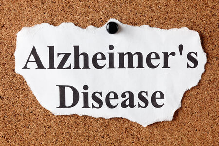 alzheimers: Torn piece of paper with the words Alzheimers Disease on corkboard (bulletin board). Stock Photo