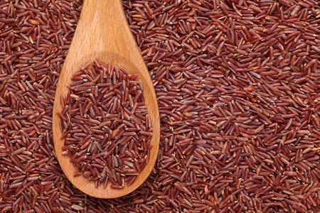 arroces: Arroz rojo en una cuchara de madera sobre fondo rojo arroz.