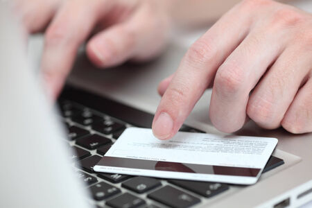 entering information: Young mans hands using a credit card for online shopping on laptop. Close-up.