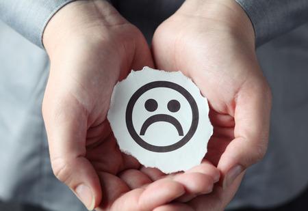 cara triste: Pedazo rasgado de papel con la cara triste en las palmas de la mujer.