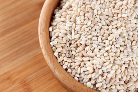 pearl barley: Pearl barley is in a wooden bowl. Close-up. Stock Photo