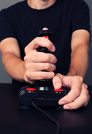 Young man plays video game with a retro joystick. Gaming joystick from the mid-1980s. Joystick with dust particles and scratches. photo