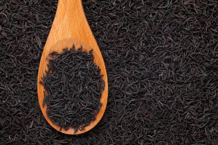 黒茶黒茶の背景に木のスプーンで。クローズ アップ。