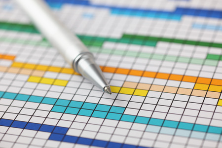 Project Plan (Gantt chart) and ballpoint pen on it. Close-up.