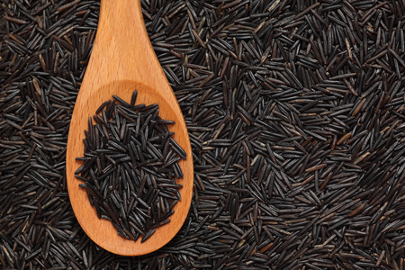 Wild rice in a wooden spoon on wild rice background. Close-up.