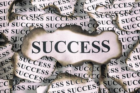 succes: Burnt Success. Burnt pieces of paper with the word Succes. Close-up. Stock Photo