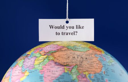 would: Piece of paper with text Would you like to travel? over globe. Stock Photo