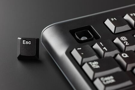 esc: Key Esc ran away from a black computer keyboard. Office Escape Concept. Stock Photo