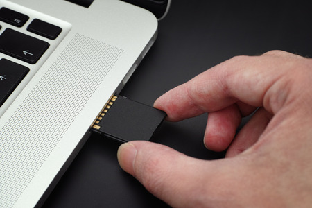 Inserting SD Card into a laptop computer. Closeup.