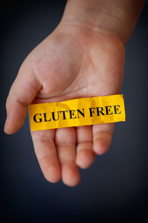 allergic ingredients: Gluten Free Concept. Child's hand holds yellow piece of paper with word «Gluten Free».