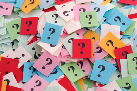 questions: Pile of colorful paper notes with question marks. Close-up. Stock Photo