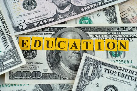 one hundred dollar bill: Cost of Education. Word Education on dollar banknotes.