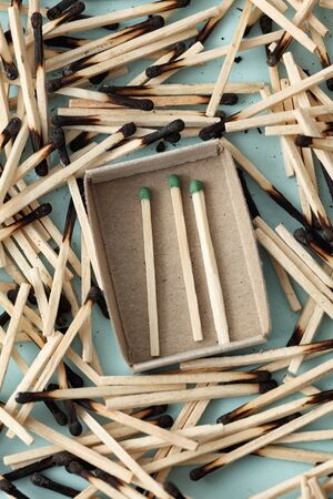 escaped: Three green matches have escaped. Three green matches in a matchbox surrounded with the burned down matches. Closeup.