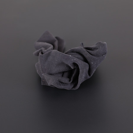 unhygienic: Black dusty rag on a black background. Stock Photo