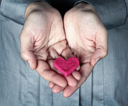 corazon roto: Mujer sosteniendo el corazón rosado agrietado en sus manos. Guardar el concepto amor. Dar del Corazón.