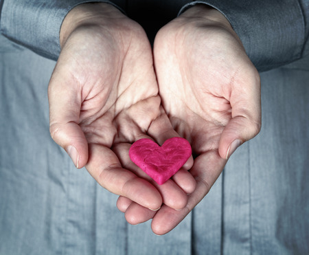 heart broken: Woman holding the cracked pink heart in her hands. Saving love concept. Giving Heart.