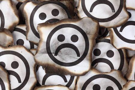 cara triste: pedazos quemados de papel con las caras tristes. De cerca.
