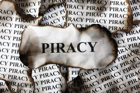 piracy: Burnt Piracy. Burnt pieces of paper with the word Piracy
