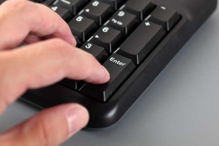 numpad: Mans hand typing on Numeric keypad of the black computer keyboard. Close-up. Stock Photo