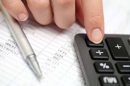 calculating: Calculating on a calculator. Financial statements. Close-up. Stock Photo
