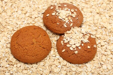 rolled oats: Oatcakes on rolled oats background. Close-up. Stock Photo