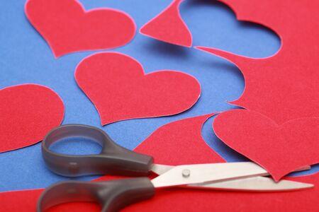 red velvet: Hearts shape cut from red velvet paper on blue velvet surface with scissors . Close-up. Stock Photo