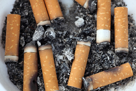bad color: Bad addiction. Ashtray and Cigarette butts close-up.