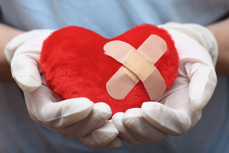bandaid: Red heart shape with cross bandaid in doctors hands. SDOF. Close-up.