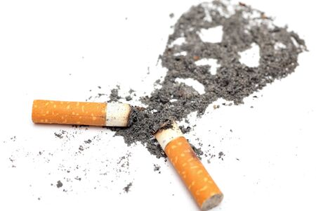 Unhealthy habit. Cigarette butts with skull shape made of ash on white background. Conceptual image. Close-up.