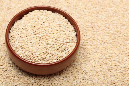 pearl barley: Pearl barley in bowl on Pearl barley background. Close-up. Stock Photo