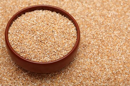 bulgur: Bulgur wheat in bowl on bulgur wheat background. Close-up. Stock Photo