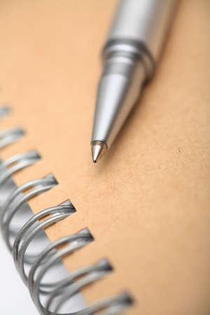 spiral notebook: Ballpoint pen on spiral notebook. Shallow depth of field. Close-up.