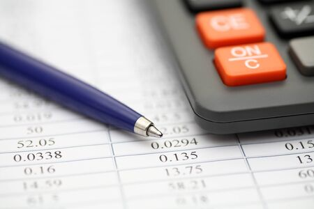 financial statements: Financial statements. Calculator, ballpoint pen on financial statements. Focus on pen. SDOF. Close-up.
