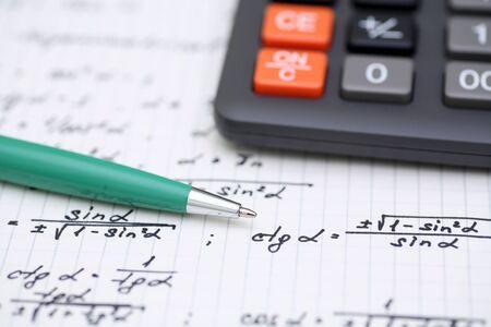 equations: Equations close-up. Homework. Solving Mathematical Problem. Focus on pen. Shallow depth of field.