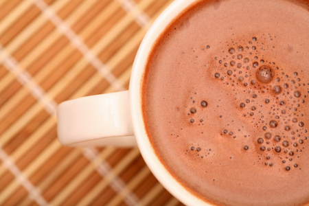 hot cocoa: Cup of cocoa with milk on bamboo napkin. Close-up. Stock Photo