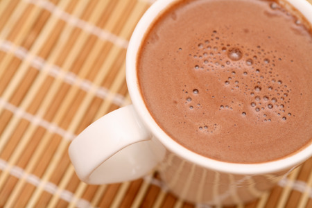 hot chocolate drink: Cup of cocoa with milk on bamboo napkin. Close-up. Stock Photo