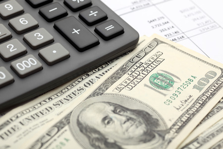 Financial statements. Calculator, dollars on financial statements. SDOF. Close-up.