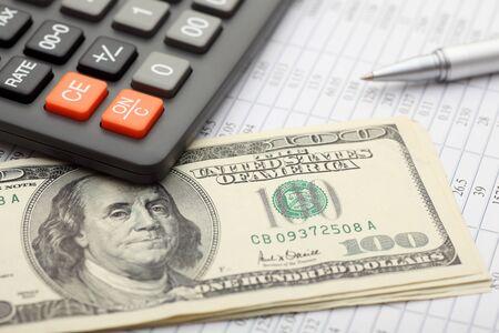 statements: Financial statements. Calculator, dollars and ballpoint pen on financial statements. SDOF. Close-up.