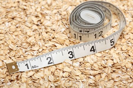 rolled oats: Healthy Eating. Tape measure on rolled oats background. Close-up.