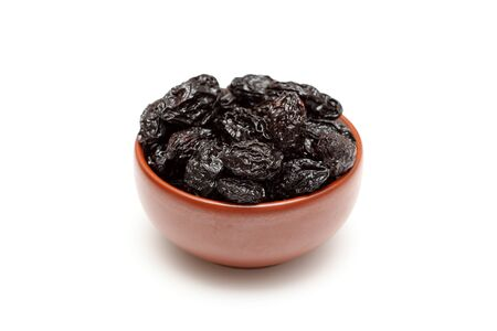 prunes: Dried prunes in bowl on white background. Close-up.