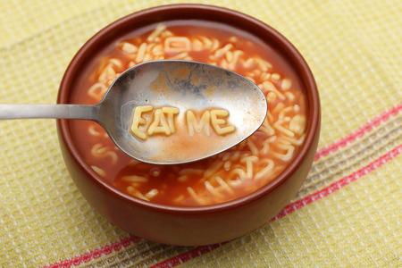 スプーンでアルファベットの文字は、「私を食べて」を綴る。ボウルにアルファベット スープ パスタ。クローズ アップ。 写真素材