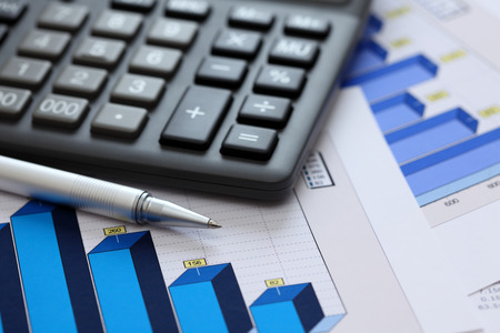 Financial statements. Business Graph. Ballpoint pen and calculator on a financial chart or Stock Market Data. Close-up.
